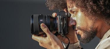 Imagen de una persona sujetando una cámara con el lente FE de 50mm F1.2 GM acoplada